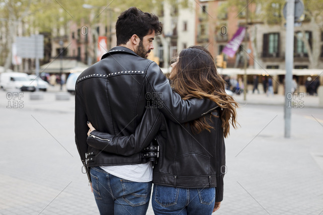Spain- Barcelona- young couple embracing and walking in the city