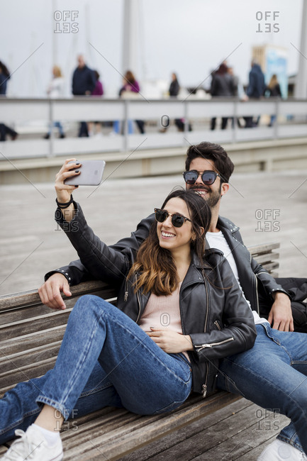 Spain- Barcelona- happy young couple resting on a bench taking a selfie