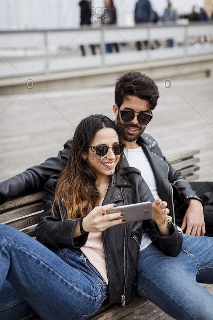 Spain- Barcelona- happy young couple with cell phone resting on a bench