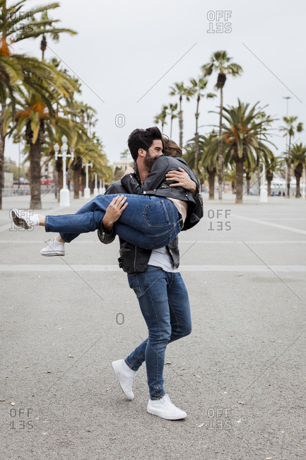 Spain- Barcelona- happy young man carrying girlfriend on promenade with palms