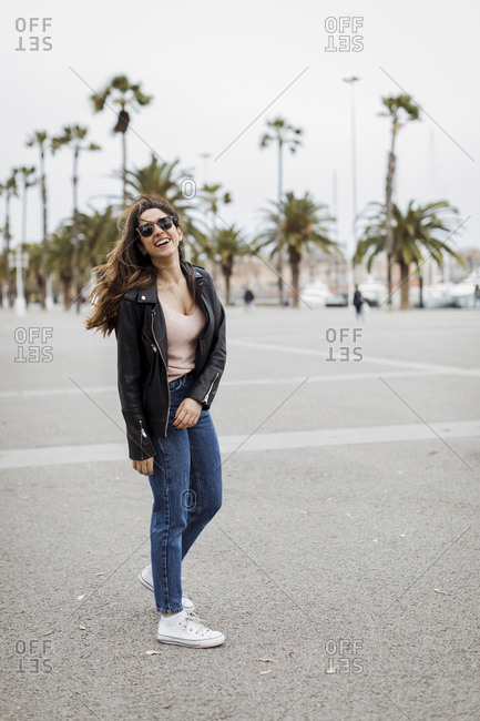 Spain- Barcelona- happy young woman standing on promenade with palms