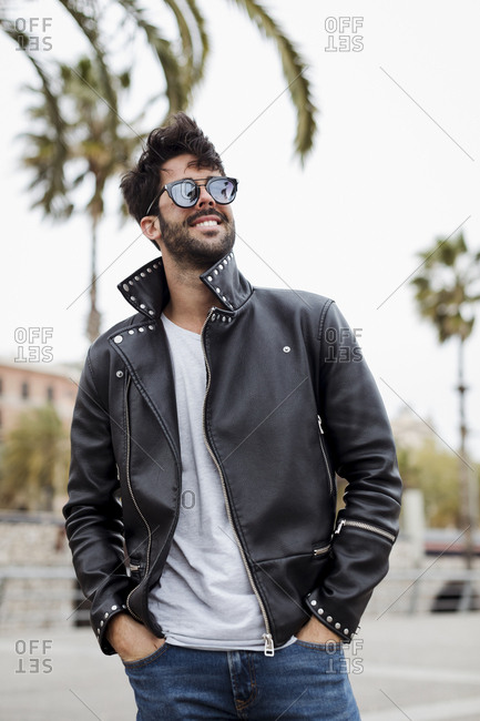 Spain- Barcelona- smiling young man standing on promenade with palms