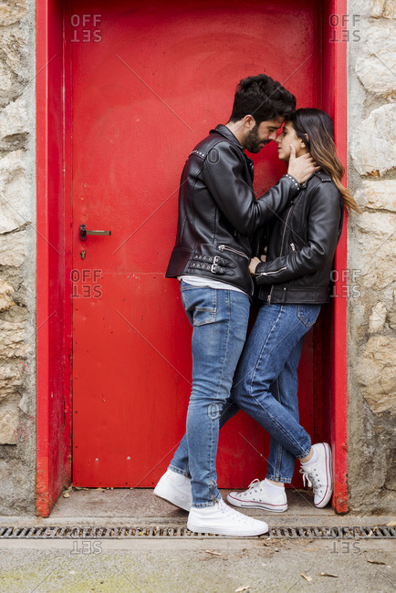Affectionate young couple kissing at red door