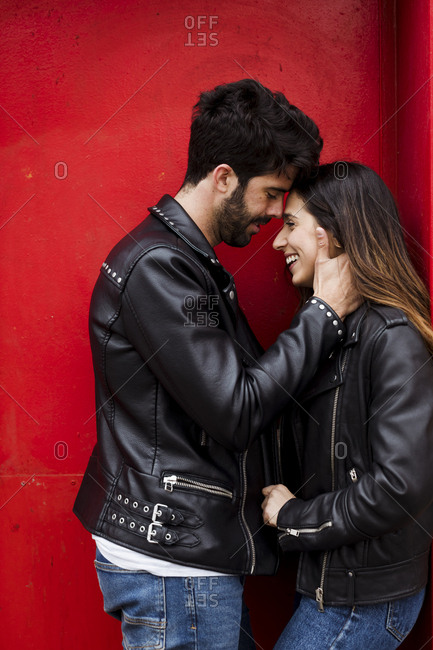 Affectionate happy young couple standing at red door