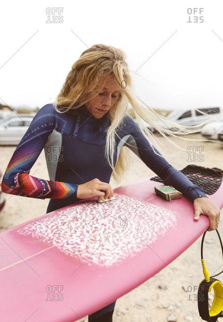 Spain- Aviles- young surfer preparing her surfboard