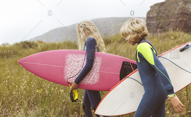 Spain- Aviles- two young surfers walking at the coast