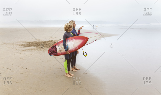 Spain- Aviles- two young surfers on the beach