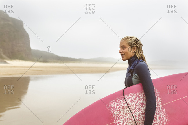 Spain- Aviles- young surfer coming out of the water on the beach