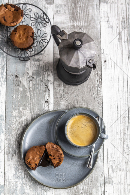 Chocolate muffin with liquid chocolate on plate with coffee cup