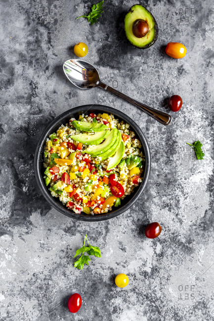 Bowl of bulgur salad with bell pepper- tomatoes- avocado- spring onion and parsley