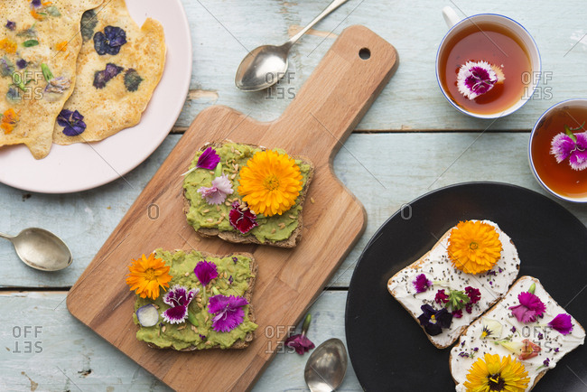 Toast with avocado hummus and spread cheese with edible flowers