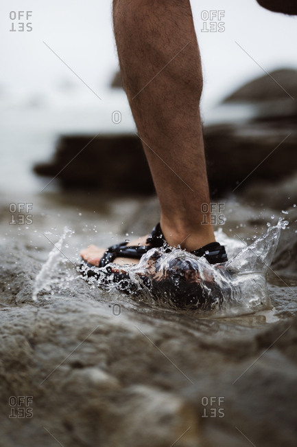 Close-up of foot of person in flip-flop splashing in water in Cantabria, Spain