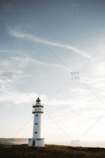 Retro beacon illuminated by sun on blue sky background in Cantabria, Spain