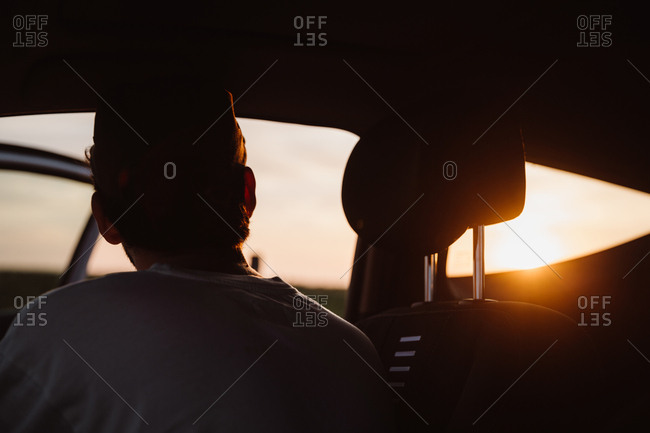 Back view of guy sitting in coupe car and watching picturesque sundown in Cantabria, Spain