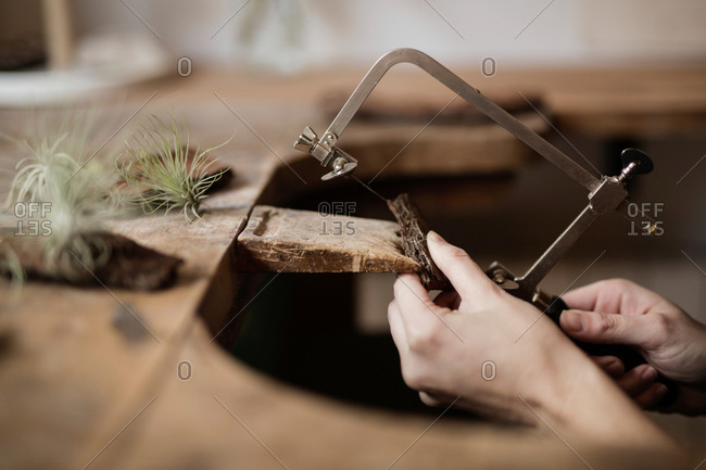 Crop close-up hands of person carving decoration of piece of tree bark with instrument on desk