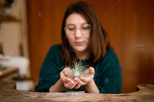 Woman in green blouse and glasses sitting at worktable in workshop and showing downy decoration