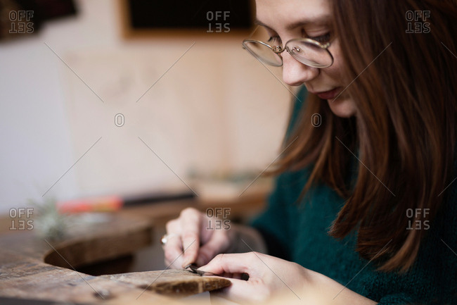 Crop close up hands of woman carving and brushing little detail with brush at desk