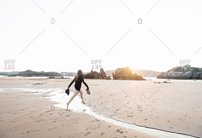 Unrecognizable barefoot lady holding hat and footwear while jumping over stream on sandy beach