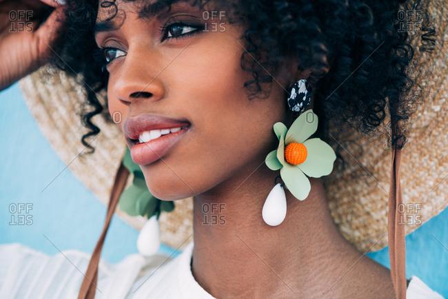Beautiful black woman wearing big earrings and a straw hat