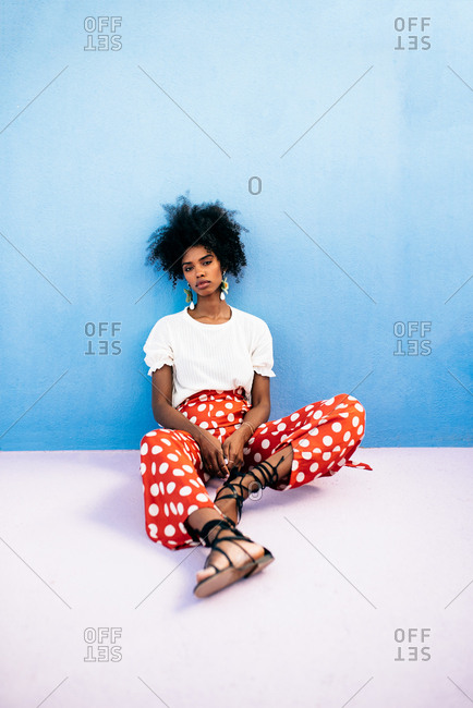 Black woman sitting in a colorful geometric building roof terrace