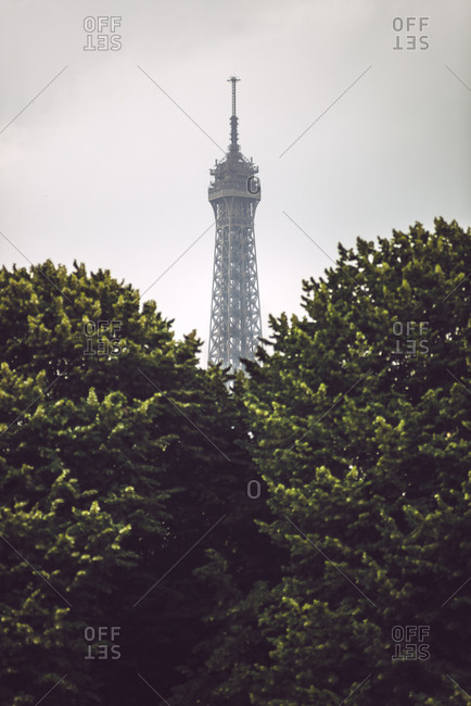 Eiffel Tower appearing from green trees on background of cloudy sky in Paris