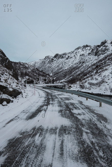 Remote cold roadway in snowy dark mountains