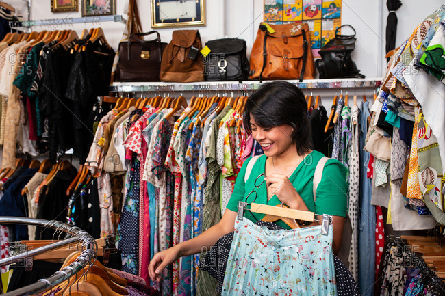 Pretty young female smiling and picking garment from clothes rail while spending time in small store