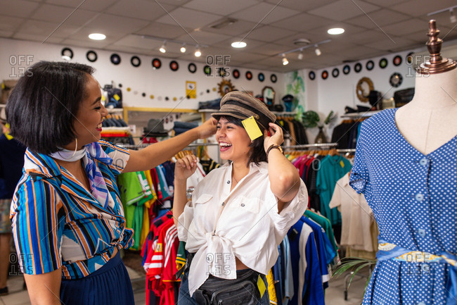 Two lovely women laughing and trying on nice hat while spending time in small store together