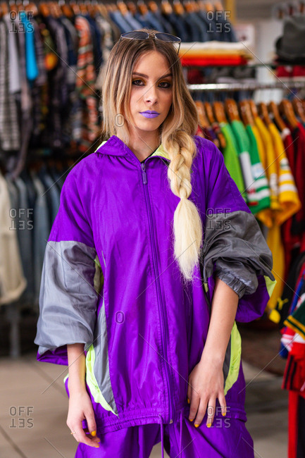 Beautiful young female in bright trendy outfit holding hands in pockets and looking at camera while standing near clothes rail in small store