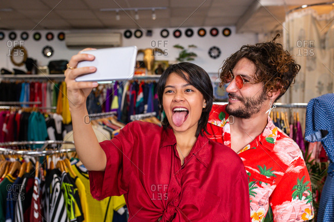 Young man and woman in stylish outfits grimacing and taking selfie while standing in small clothes store