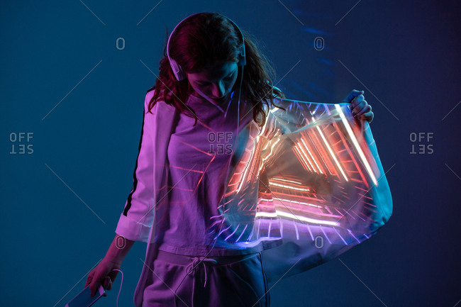 Young woman in headphones looking at neon light projection on blazer in studio