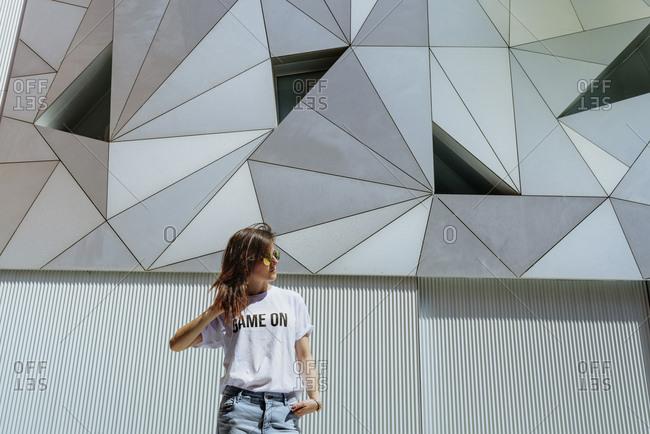 Cheerful woman posing near modern wall