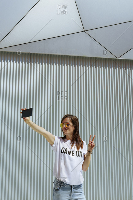 Cheerful woman taking selfie and posing near modern wall