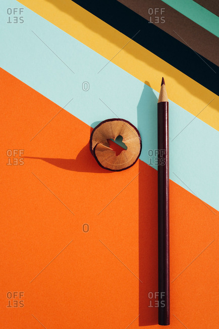 Pencil and shavings from sharpening, on colored striped papers background. Back to school concept