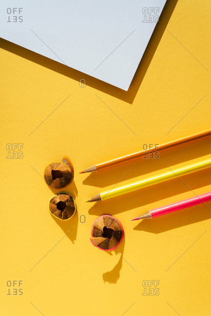 Back to school, Color pencil and shavings from sharpening on yellow background