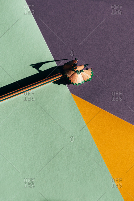 Pencil and shavings from sharpening, on colored geometric papers background. Back to school concept