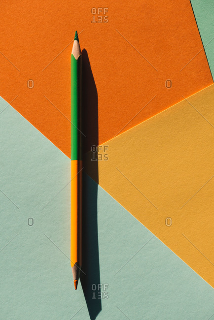 double-ended colored pencil, on light blue and orange geometric background, back to school concept