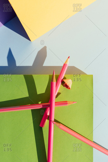 Pink pencils on green book, in space of geometric shapes and strong shadows. Back to School concept