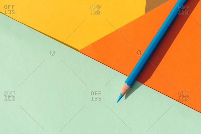 colored pencil, on light blue and orange geometric background, back to school concept