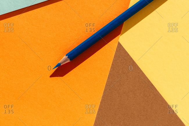 Blue pencil, on light yellow and orange geometric background, back to school concept