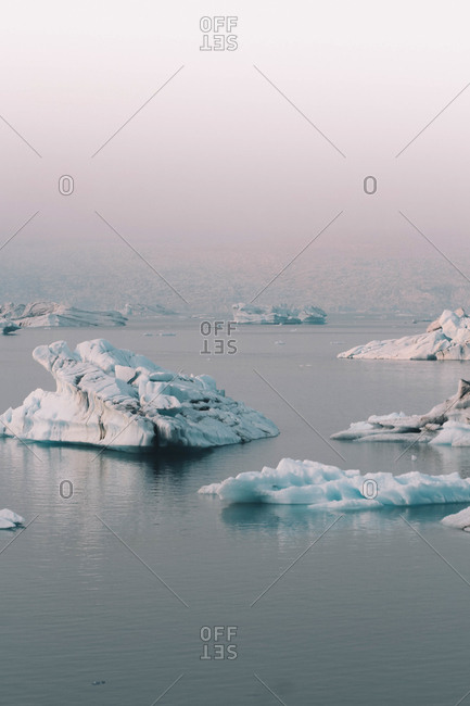 View of cold icy glacier pieces floating in cold water of ocean