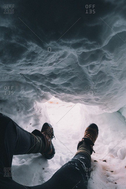 Crop shot of traveler's legs in boots sitting in snowy cave with light below