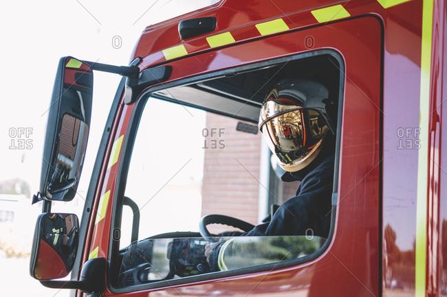Firemen driving inside an emergency vehicle.