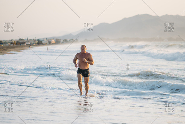 Strong old man makes exercise on the beach.