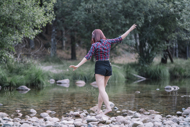 Pretty red haired girl performs exercises by the river.
