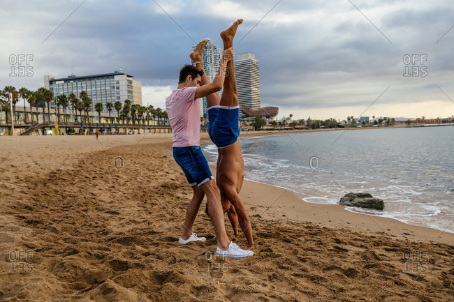 Two athletes do a handstand on the beach.
