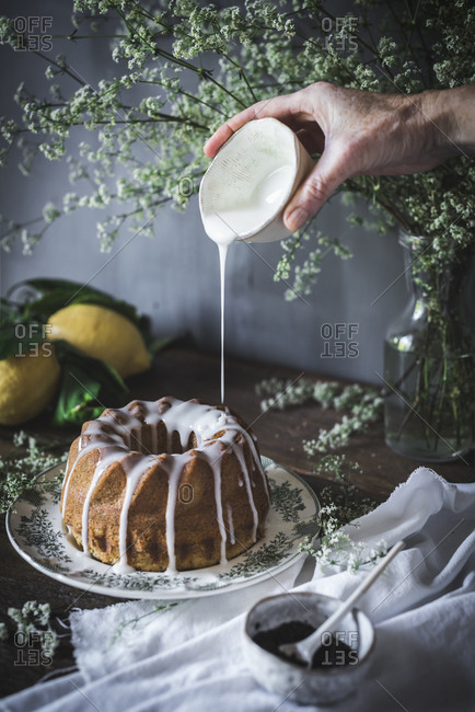 Crop view of hand holding cup of sweet dressing and pouring on delicious pie placed on dish near cup of poppy seed and flowers in vase