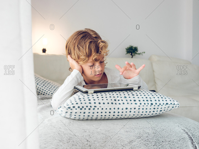 Cute boy with tablet on sofa