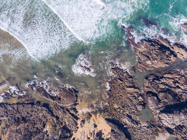 From above shot of sea water waving near rocky coast in Asturias, Spain