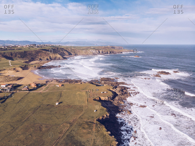 Amazing drone view of beautiful sea waving near shore with farming fields and settlement on sunny day in Asturias, Spain